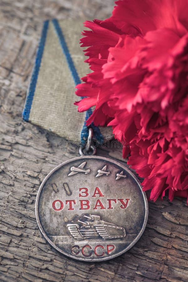Το παλαιό σοβιετικό μετάλλιο για την ανδρεία του δεύτερου παγκόσμιου πολέμου με ένα κόκκινο γαρίφαλο, έννοια καρτών στις 9 Μαΐου  στοκ εικόνες με δικαίωμα ελεύθερης χρήσης