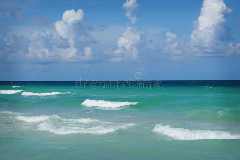 Το πανέμορφο τυρκουάζ χρωμάτισε τα νερά ενάντια σε έναν μπλε ουρανό με τα άσπρα σύννεφα στην παραλία Hollywood, Φλώριδα στοκ εικόνα