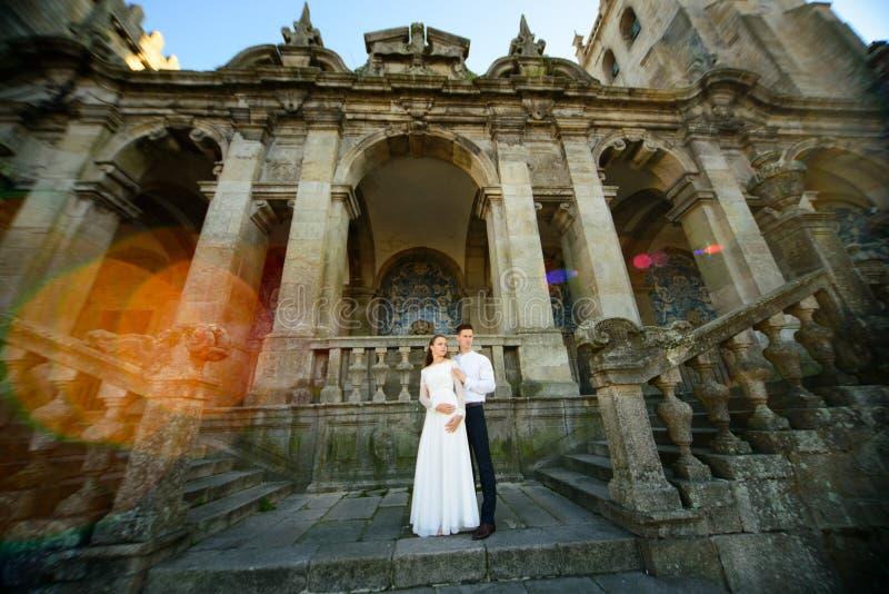 Το παντρεμένο ζευγάρι διασκέδασης πρόσφατα αγκαλιάζει κοντά στην εκκλησία στοκ εικόνα με δικαίωμα ελεύθερης χρήσης
