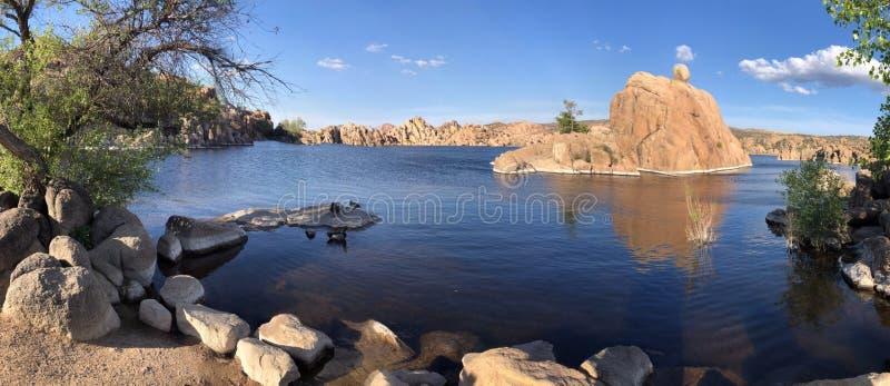Το πανόραμα μιας μπλε λίμνης βουνών αλλά ομαλοί βράχοι στοκ εικόνα