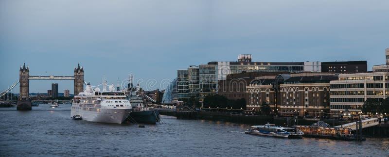 Το πανόραμα του κρουαζιερόπλοιου έδεσε στον ποταμό Τάμεσης κατά τη διάρκεια της μπλε ώρας, γέφυρα πύργων στο υπόβαθρο, Λονδίνο, U στοκ εικόνα με δικαίωμα ελεύθερης χρήσης