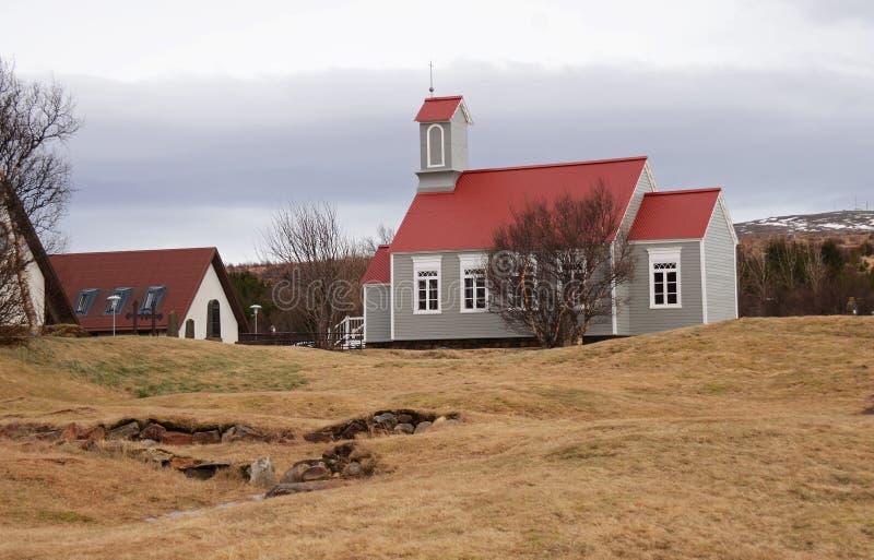 Το παραδοσιακό ισλανδικό σπίτι με την κόκκινη στέγη στέκεται στους λόφους μιας κίτρινης ξηράς χλόης στο υπόβαθρο του ουρανού στοκ εικόνες