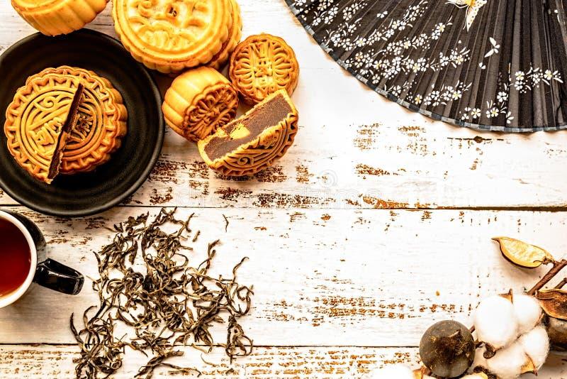 Το παραδοσιακό κινέζικο mooncakes με το τσάι και οι διακοσμήσεις στο άσπρο ξύλινο επίπεδο υποβάθρου βάζουν τη τοπ άποψη στοκ φωτογραφία με δικαίωμα ελεύθερης χρήσης