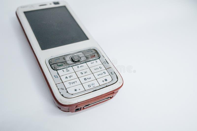 Το παραδοσιακό κινητό τηλέφωνο στη δεύτερη γενιά με το κουμπί πληκτρολογίων και το μίνι γραπτό όργανο ελέγχου από το λευκό απομον στοκ εικόνα