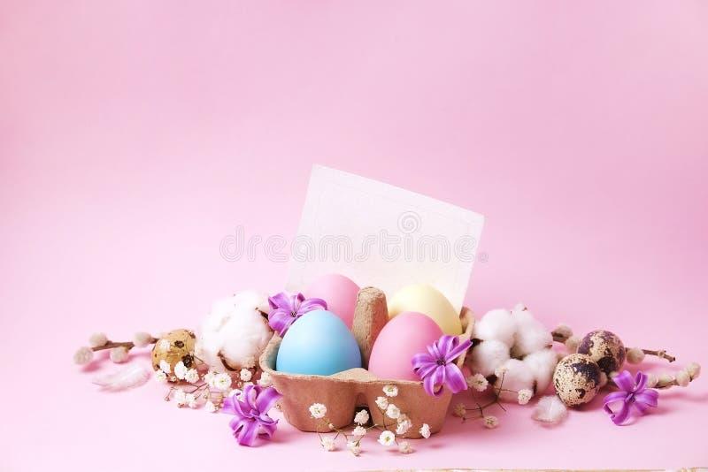 Το παραδοσιακό πρότυπο καρτών Πάσχας με τα χρώματα κρητιδογραφιών χρωμάτισε τα οργανικά αυγά στο ψάθινο καλάθι με το σανό και τα  στοκ εικόνες με δικαίωμα ελεύθερης χρήσης
