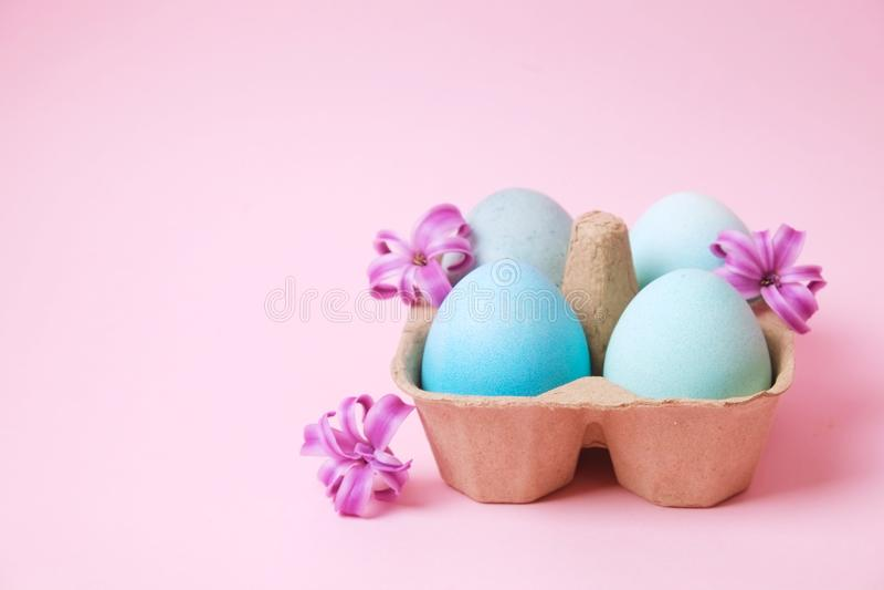 Το παραδοσιακό πρότυπο καρτών Πάσχας με τα χρώματα κρητιδογραφιών χρωμάτισε τα οργανικά αυγά στο ψάθινο καλάθι με το σανό και τα  στοκ εικόνα με δικαίωμα ελεύθερης χρήσης