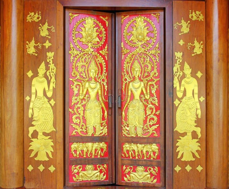 Το παραδοσιακό ταϊλανδικό ύφος χαράζει στην ξύλινη πόρτα, ναός της Ταϊλάνδης στοκ εικόνα