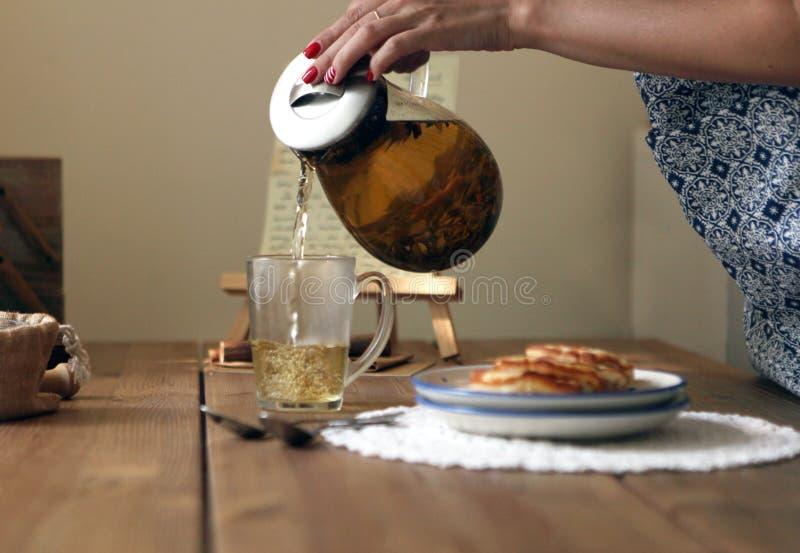 Το παραδοσιακό heral τσάι με teapot γυαλιού, φλυτζάνι, ξηρό αυξήθηκε οφθαλμοί και pancaces Λουλούδια στο ξύλινο επιτραπέζιο στο σ στοκ φωτογραφίες με δικαίωμα ελεύθερης χρήσης