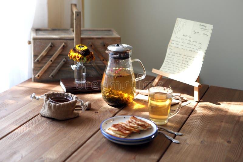 Το παραδοσιακό heral τσάι με teapot γυαλιού, φλυτζάνι, ξηρό αυξήθηκε οφθαλμοί και pancaces Λουλούδια στο ξύλινο επιτραπέζιο στο σ στοκ φωτογραφία με δικαίωμα ελεύθερης χρήσης