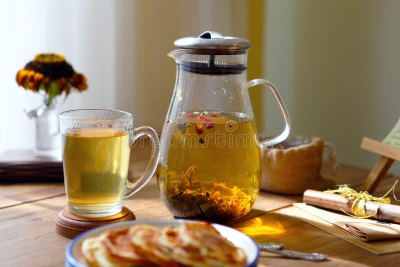 Το παραδοσιακό heral τσάι με teapot γυαλιού, φλυτζάνι, ξηρό αυξήθηκε οφθαλμοί και pancaces Λουλούδια στο ξύλινο επιτραπέζιο στο σ στοκ φωτογραφίες