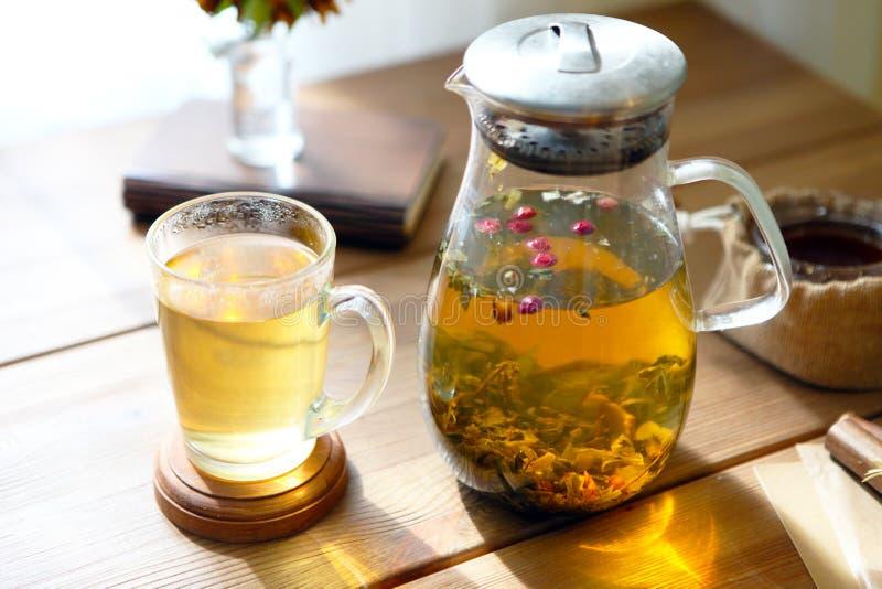 Το παραδοσιακό heral τσάι με teapot γυαλιού, φλυτζάνι, ξηρό αυξήθηκε οφθαλμοί Λουλούδια στον ξύλινο πίνακα στο σπίτι, υπόβαθρο φω στοκ εικόνες