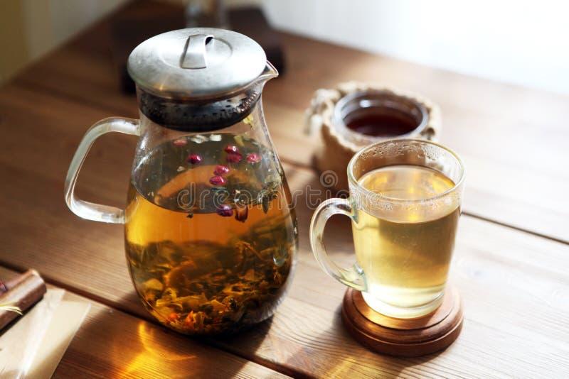 Το παραδοσιακό heral τσάι με teapot γυαλιού, φλυτζάνι, ξηρό αυξήθηκε οφθαλμοί Λουλούδια στον ξύλινο πίνακα στο σπίτι, υπόβαθρο φω στοκ φωτογραφία με δικαίωμα ελεύθερης χρήσης