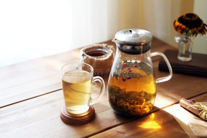 Το παραδοσιακό heral τσάι με teapot γυαλιού, φλυτζάνι, ξηρό αυξήθηκε οφθαλμοί Λουλούδια στον ξύλινο πίνακα στο σπίτι, υπόβαθρο φω στοκ εικόνα