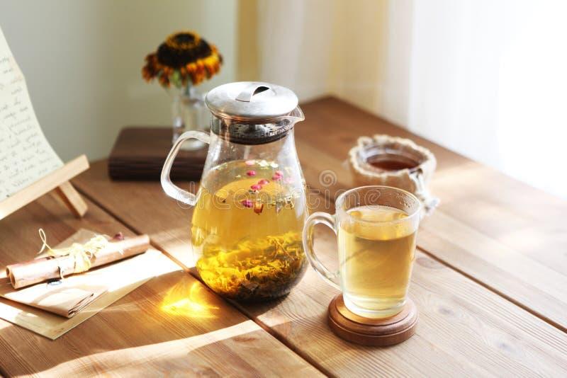 Το παραδοσιακό heral τσάι με teapot γυαλιού, φλυτζάνι, ξηρό αυξήθηκε οφθαλμοί Λουλούδια στον ξύλινο πίνακα στο σπίτι, υπόβαθρο φω στοκ φωτογραφία
