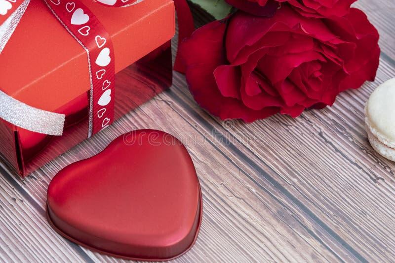 Το παρόν κιβώτιο, κόκκινο αυξήθηκε, και ένα κόκκινο καρδιά-διαμορφωμένο κομμάτι μετάλλων στοκ φωτογραφία