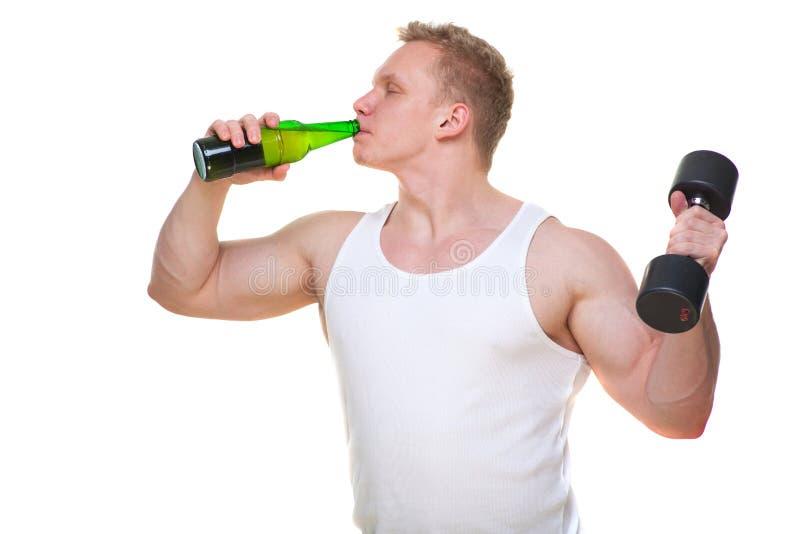 Το παχύ άτομο με ένα μπουκάλι της μπύρας κρατά τους αλτήρες απομονωμένους στο λευκό Η έννοια της επιλογής μεταξύ των επιβλαβών τρ στοκ εικόνες