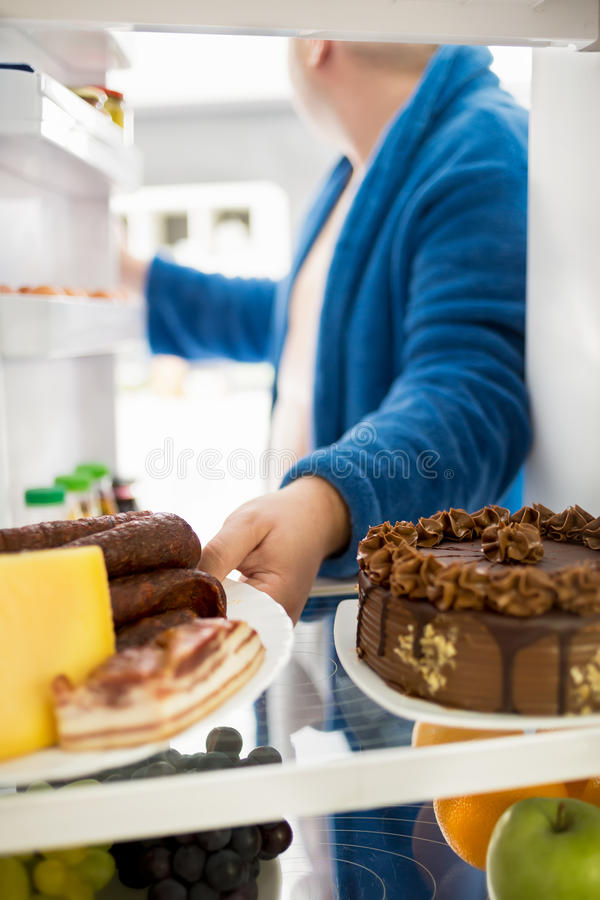 Το παχύ άτομο παίρνει το σύνολο πιάτων των σκληρών τροφίμων από το ψυγείο στοκ εικόνα