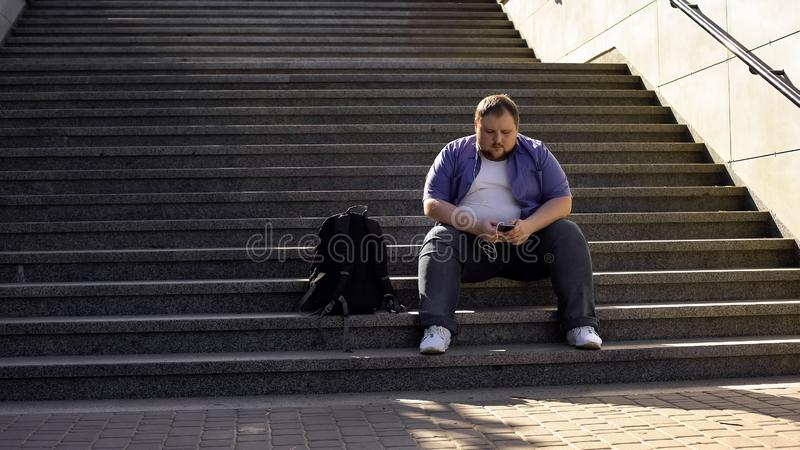 Το παχύ άτομο που ακούει τη μουσική στα σκαλοπάτια, μοναξιά, υπερβολικό βάρος προκαλεί τις αβεβαιότητες στοκ εικόνα