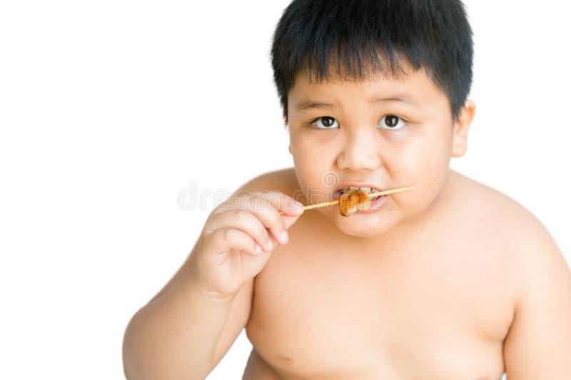 Το παχύ αγόρι τρώει το ψημένο στη σχάρα χοιρινό κρέας που απομονώνεται στοκ φωτογραφίες με δικαίωμα ελεύθερης χρήσης