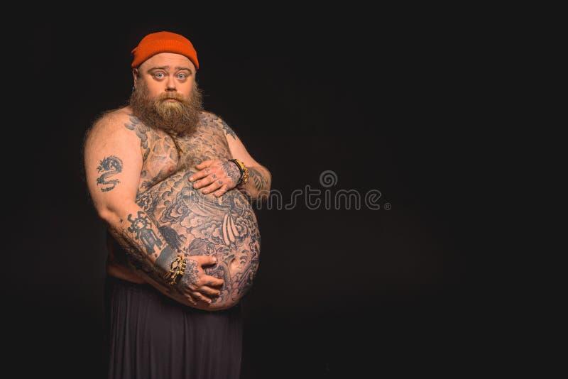Το παχύ αρσενικό hipster συμπαθεί την κοιλιά του στοκ εικόνες