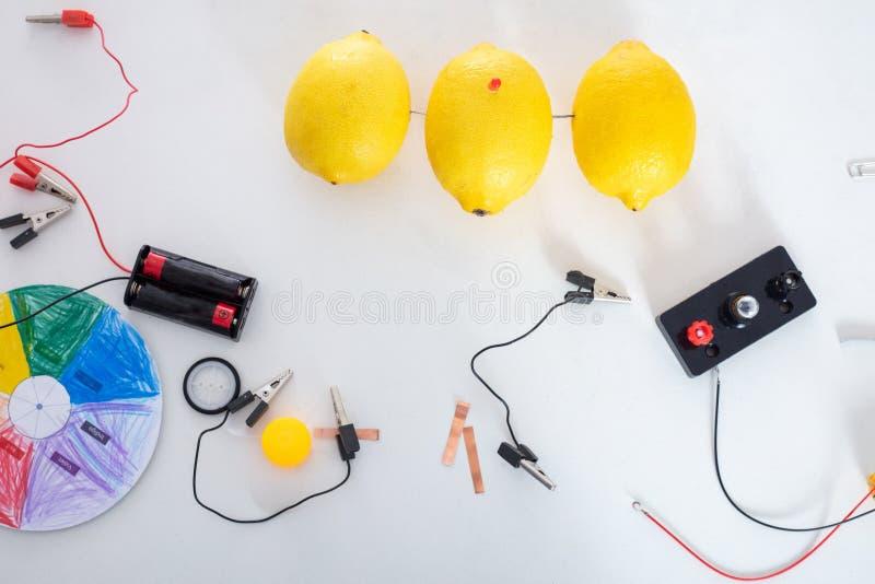 Το πείραμα της παραγωγής της ηλεκτρικής ενέργειας με τα λεμόνια για τα παιδιά στοκ εικόνες
