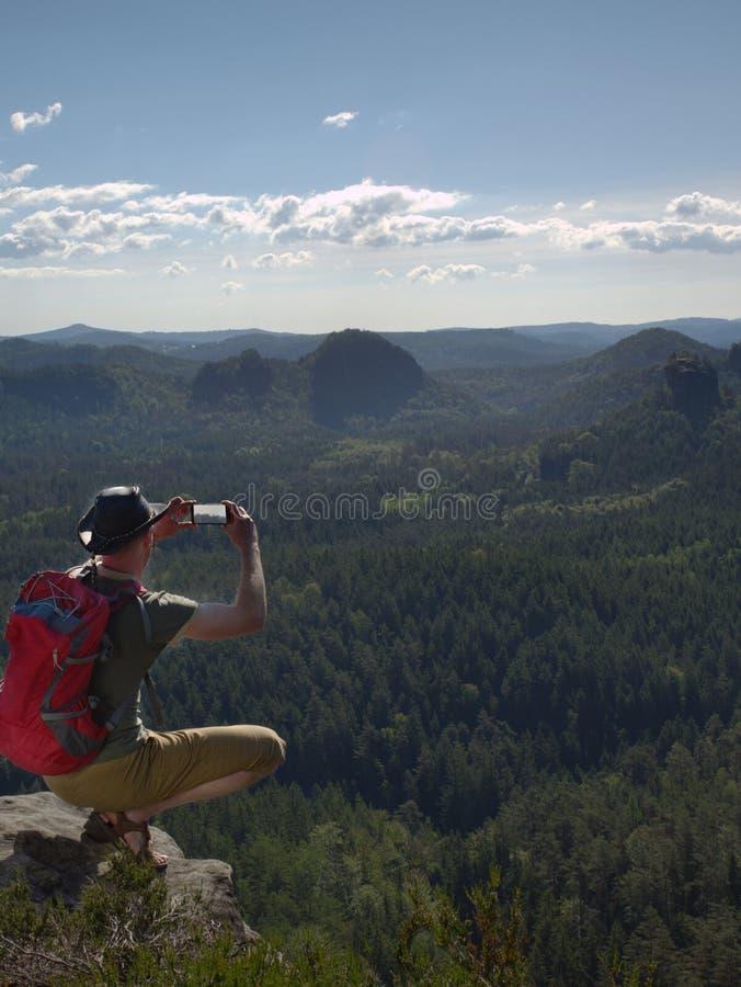 Το πεζοποριες άτομο με το σακίδιο πλάτης, το καπέλο και το τηλέφωνο κάθονται στον απότομο βράχο βουνών στοκ φωτογραφίες