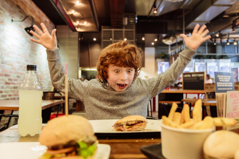 Το πεινασμένο αγόρι τρώει burger στο εστιατόριο στοκ εικόνα
