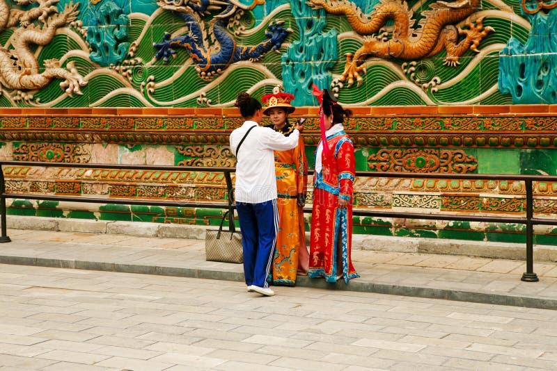 Το Πεκίνο, Κίνα, το 06/06/2018 δύο κινεζικά κορίτσια στα εθνικά κοστούμια φωτογραφίζεται κοντά στον τοίχο εννέα δράκων απαγορευμέ στοκ φωτογραφία με δικαίωμα ελεύθερης χρήσης
