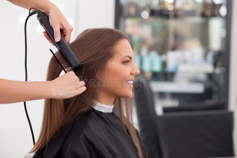 Το πεπειραμένο νέο hairstylist την εξυπηρετεί στοκ εικόνες
