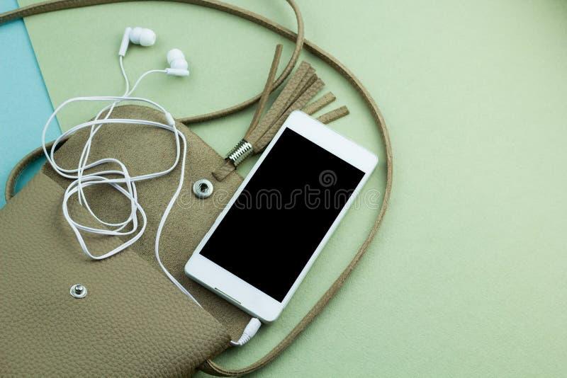 το περιεχόμενο της τσάντας γυναικών τηλεφωνά στην πλαστά επάνω μαύρα οθόνη και τα ακουστικά σε μια ανοικτή τσάντα στο πράσινο και στοκ φωτογραφία