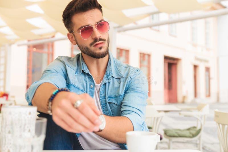 Το περιστασιακό άτομο που έχει τον καφέ στην πόλη κοιτάζει στην πλευρά στοκ εικόνα