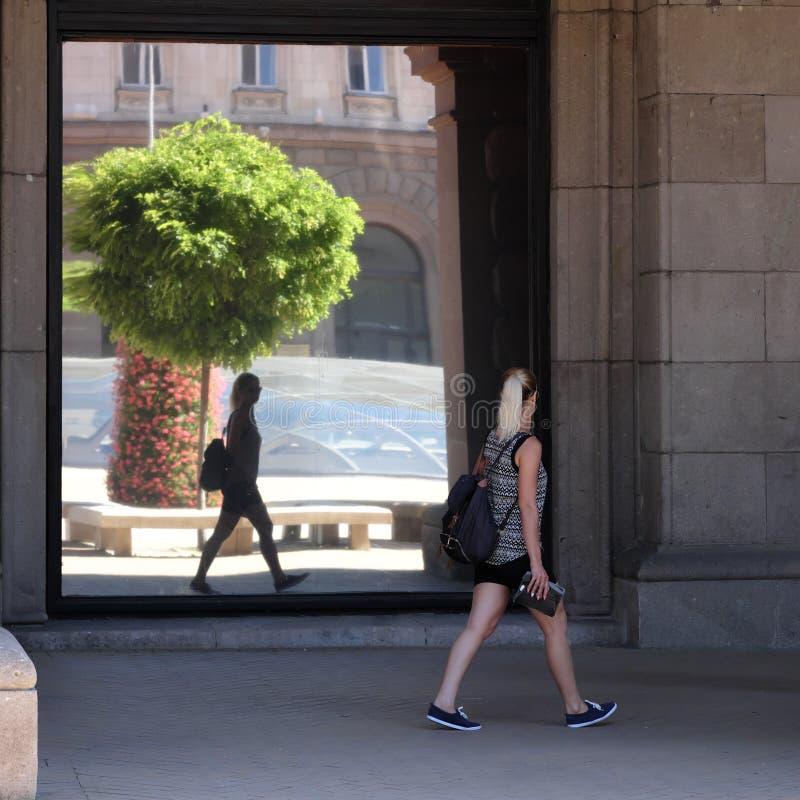 Το περπάτημα γυναικών και εξετάζει την στα παράθυρα γυαλιού καθρεφτών στοκ φωτογραφίες με δικαίωμα ελεύθερης χρήσης