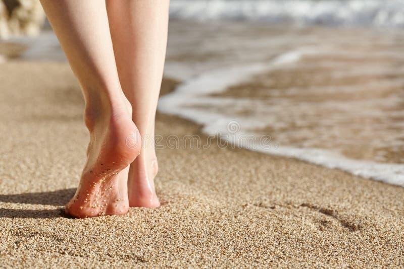 Το περπάτημα γυναικών σε μια αμμώδη παραλία, πόδια κοντά επάνω βλέπει στοκ εικόνα με δικαίωμα ελεύθερης χρήσης