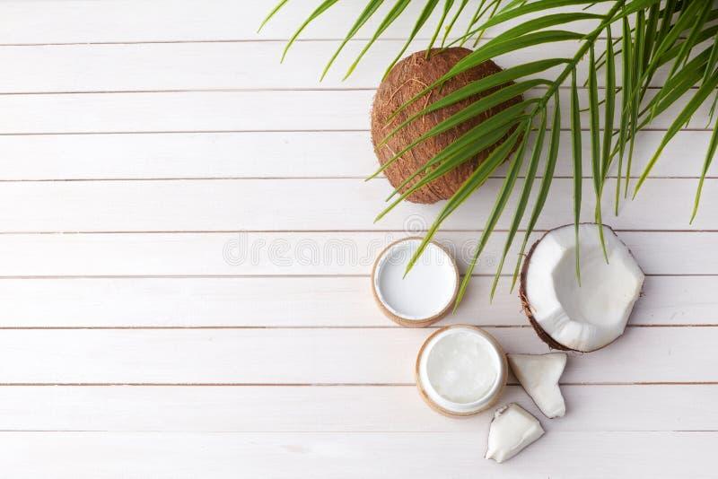 Το πετρέλαιο καρύδων με το φρέσκο cocnut, φυσικό καλλυντικό, επίπεδο βάζει την εικόνα στο ξύλινο υπόβαθρο στοκ φωτογραφία