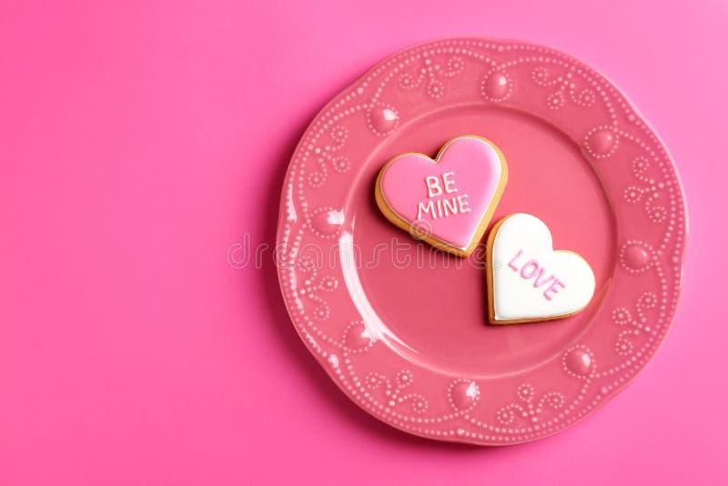 Το πιάτο με τη διακοσμημένη καρδιά διαμόρφωσε τα μπισκότα και το διάστημα για το κείμενο στο υπόβαθρο χρώματος, τοπ άποψη στοκ εικόνα