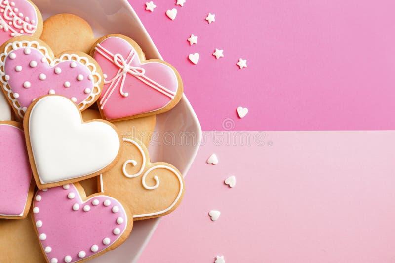 Το πιάτο με τη διακοσμημένη καρδιά διαμόρφωσε τα μπισκότα και το κομφετί καραμελών στο υπόβαθρο χρώματος, τοπ άποψη στοκ φωτογραφία με δικαίωμα ελεύθερης χρήσης