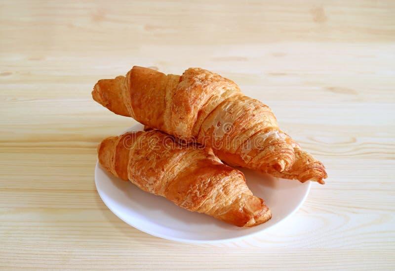 Το πιάτο ολόκληρων των croissant ζυμών σίτου εξυπηρέτησε στον ξύλινο πίνακα με ελεύθερου χώρου για το κείμενο ή το σχέδιο στοκ εικόνα με δικαίωμα ελεύθερης χρήσης