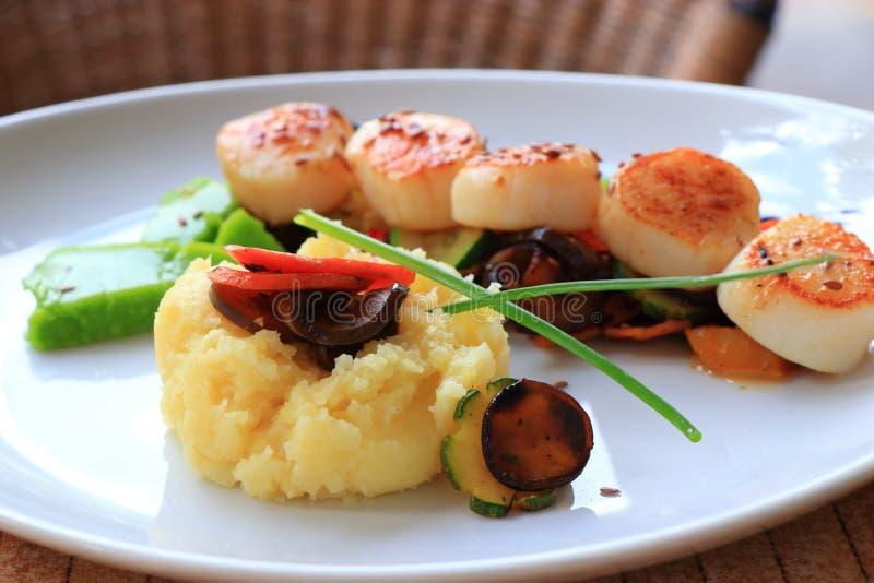 Το πιάτο των οστράκων που μαγειρεύονται με τα λαχανικά του διακοσμεί σε ένα γαλλικό εστιατόριο στοκ φωτογραφία