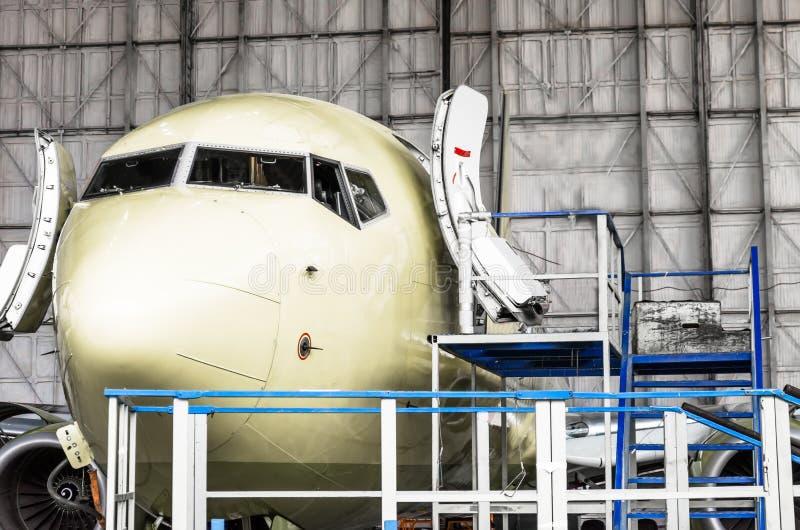 Το πιλοτήριο και η μύτη των αεροσκαφών κλείνουν επάνω σε ένα υπόστεγο στην υπηρεσία, με τις ανοιχτές πόρτες στοκ φωτογραφίες με δικαίωμα ελεύθερης χρήσης