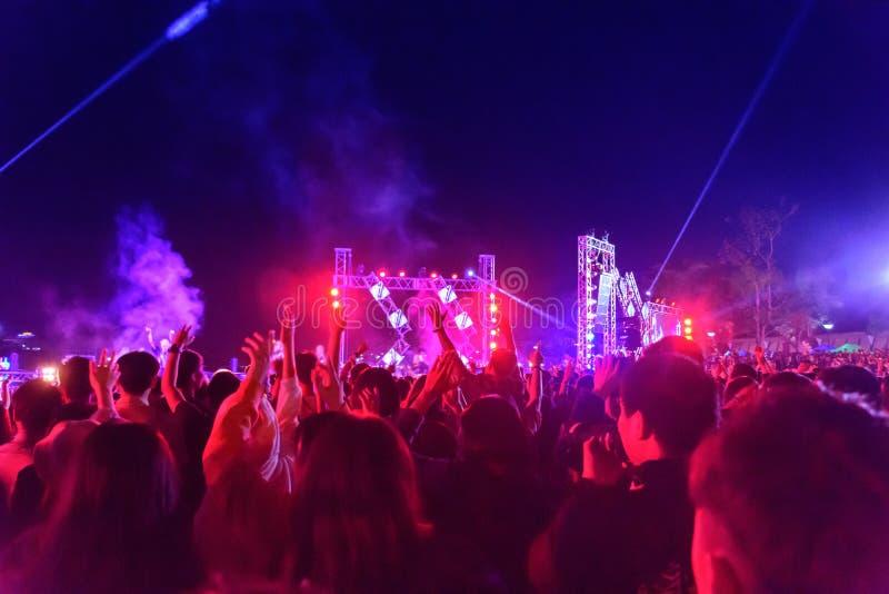 Το πλήθος συναυλίας που παρευρίσκεται σε μια μίνι συναυλία, άνθρωποι είναι ορατό, αναδρομικά φωτισμένος από τα μπλε κόκκινα φώτα  στοκ εικόνες