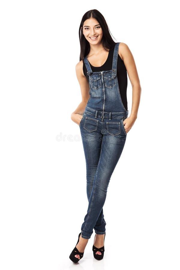 Το πλήρες μήκος μιας ευτυχούς νέας γυναίκας που στέκεται με παραδίδει τις τσέπες στοκ φωτογραφία με δικαίωμα ελεύθερης χρήσης