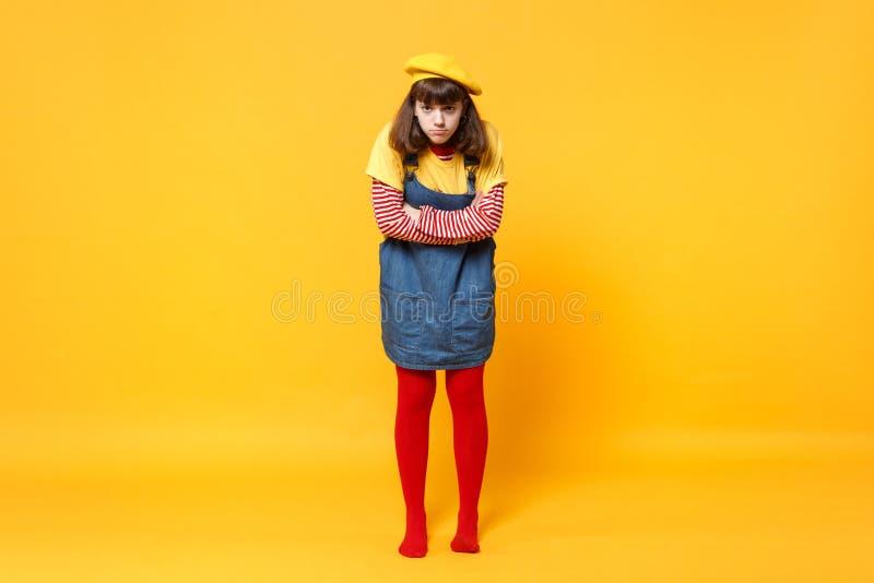 Το πλήρες πορτρέτο μήκους εφήβου κοριτσιών γαλλικό beret, χέρια εκμετάλλευσης τζιν sundress διέσχισε απομονωμένος του σε κίτρινο στοκ εικόνες