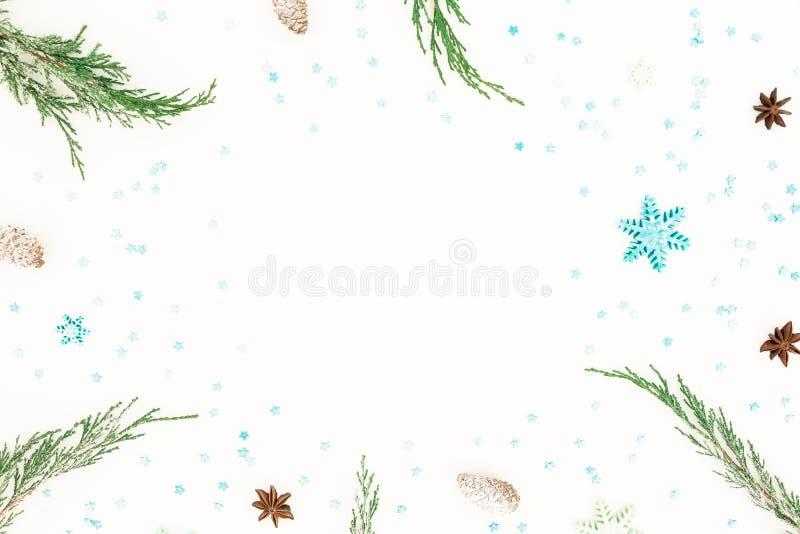 Το πλαίσιο Χριστουγέννων του αειθαλούς δέντρου διακλαδίζεται, μπλε snowflakes και κώνος πεύκων στο άσπρο υπόβαθρο Επίπεδος βάλτε, στοκ εικόνες