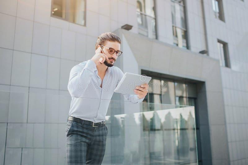 Το πολυάσχολο και όμορφο άτομο στέκεται και κρατά την ταμπλέτα Εξετάζει την οθόνη του και μιλά στο τηλέφωνο συγχρόνως Αυτός ο τύπ στοκ εικόνες