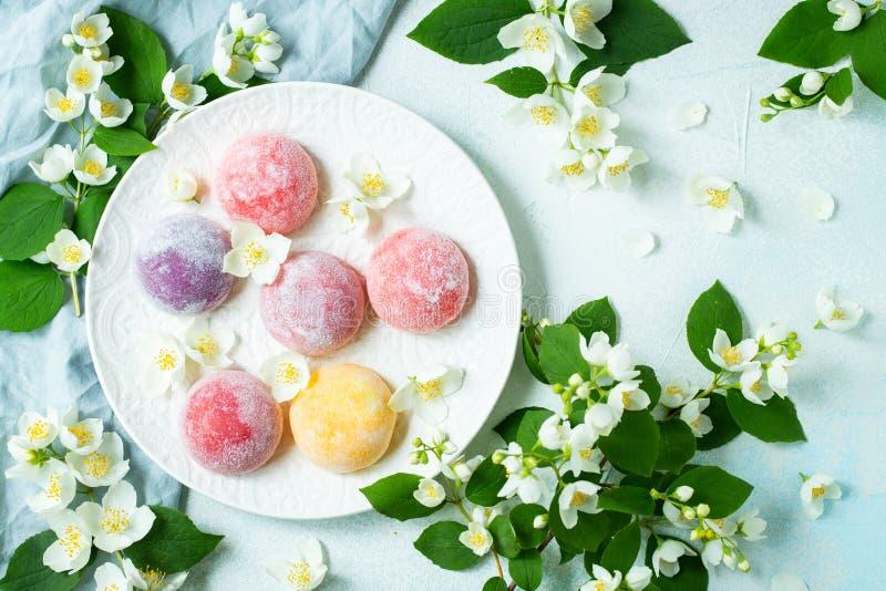 Το πολύχρωμο ιαπωνικό παγωτό Mochi στη ζύμη και τη Jasmine ρυζιού ανθίζει σε ένα συγκεκριμένο μπλε υπόβαθρο Τα παραδοσιακά ιαπωνι στοκ φωτογραφία