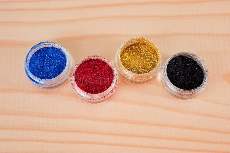 Το πολύχρωμο μαργαριτάρι ακτινοβολεί για το μανικιούρ στα βάζα που λαμβάνονται σε μια ξύλινη επιφάνεια στοκ εικόνες