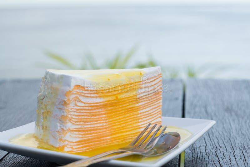 Το πορτοκάλι crepe το κέικ στο άσπρο πιάτο στο μαύρο ξύλινο πίνακα με το υπόβαθρο θάλασσας στοκ εικόνα