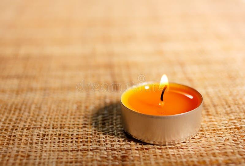 Το πορτοκαλί κερί που τοποθετείται καίγοντας στο υλικό γιούτας στοκ εικόνες