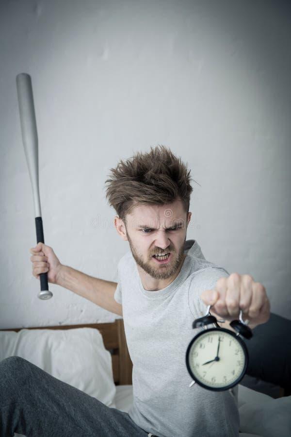 Το πορτρέτο ανέτρεψε με χτυπημένο τον μπέιζ-μπώλ νεαρό άνδρα που κραυγάζει στο ξυπνητήρι στην κρεβατοκάμαρα στοκ εικόνα με δικαίωμα ελεύθερης χρήσης