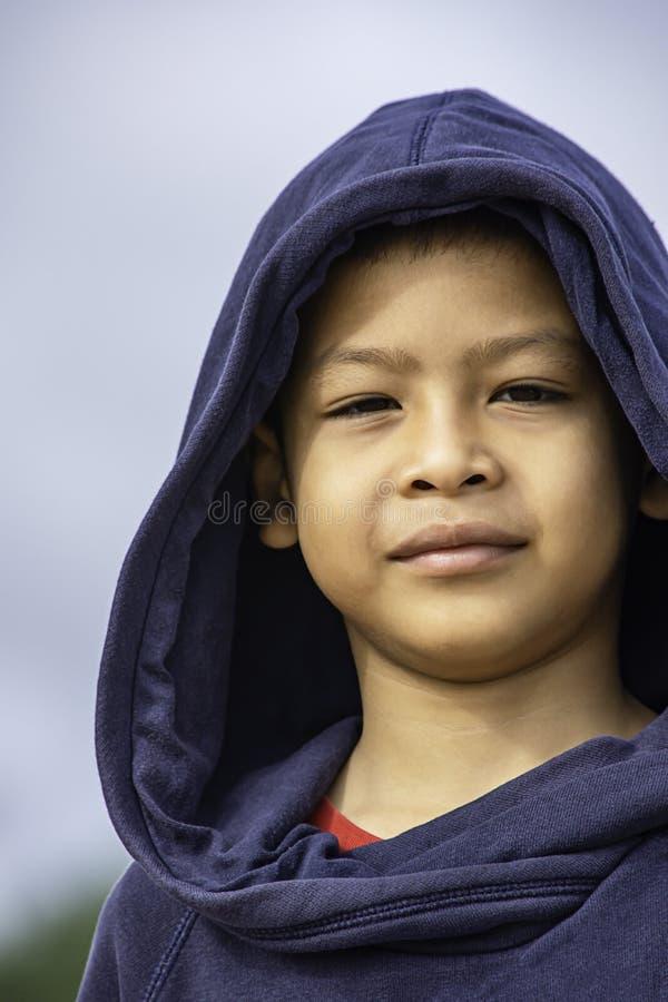 Το πορτρέτο ενός αγοριού της Ασίας που φορά ένα χειμερινό σακάκι χαμογελούσε ευτυχώς στοκ φωτογραφίες
